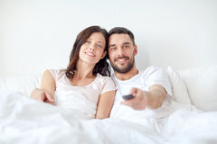 Happy couple lying in bed at home and watching tv Royalty Free Stock Images