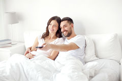 Happy couple lying in bed at home and watching tv Royalty Free Stock Photo