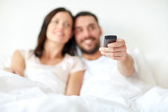 Happy couple lying in bed at home and watching tv Stock Image