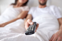 Happy couple lying in bed at home and watching tv Stock Photography