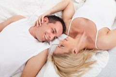Happy couple lying on bed Royalty Free Stock Photos