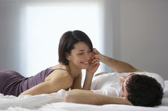 Happy Couple Lying In Bed Stock Photo