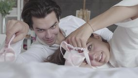 Happy couple lying in the bed playing with pink children`s pointe close-up. Young family waiting for a baby girl. Tender stock video footage