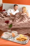 Happy couple lying bed romantic breakfast hotel Royalty Free Stock Image