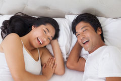 Happy couple lying in bed smiling at camera Royalty Free Stock Image
