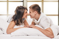 Happy Couple lying in bed Stock Image