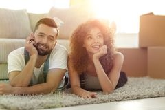 Young couple lying on the rug on the background of a new apartme. Happy couple lying on the carpet on the background of a new apartment royalty free stock photography