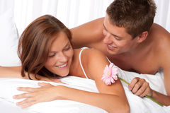 Happy couple lying down in bed together Royalty Free Stock Photos