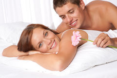 Happy couple lying down in bed together Stock Photography