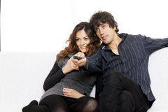 Happy couple lying down in bedroom watching television together Stock Photography