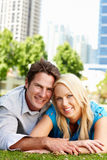 Happy couple Lying down in park Stock Photos