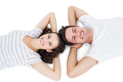 Happy couple lying on the floor head to head Stock Images
