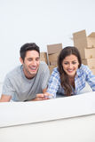 Happy couple lying on the floor and holding a house plan Stock Image