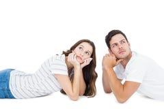 Happy couple lying on the floor looking away Stock Photography