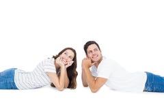 Happy couple lying on the floor looking away Stock Image