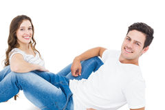 Happy couple lying on the floor looking at the camera Stock Photos