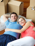 Happy couple lying on floor after moving house Royalty Free Stock Images