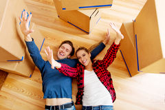 Happy couple lying on the floor in new home with cordboard boxes around Stock Image