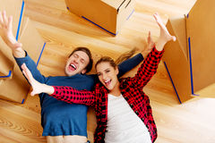 Happy couple lying on the floor in new home with cordboard boxes around Stock Images