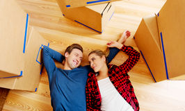 Happy couple lying on the floor in new home with cordboard boxes around Stock Photos