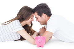 Happy couple lying on the floor with piggy bank Royalty Free Stock Images