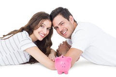 Happy couple lying on the floor with piggy bank Stock Photos