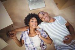 Happy couple lying on the floor Stock Photos