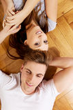 Happy couple lying on the floor. Royalty Free Stock Photos
