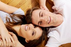Happy couple lying on the floor. Royalty Free Stock Photography