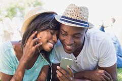 Happy couple lying in garden together listening to music Royalty Free Stock Image