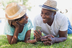 Happy couple lying in garden together listening to music Stock Photo
