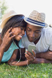 Happy couple lying in garden together listening to music Stock Images