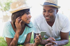 Happy couple lying in garden together listening to music Stock Photography