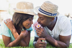 Happy couple lying in garden together smelling flowers Royalty Free Stock Images