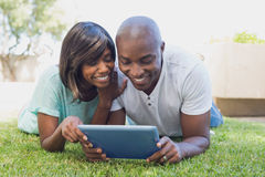 Happy couple lying in garden using tablet pc together Stock Photos