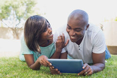 Happy couple lying in garden using tablet pc together Stock Photo