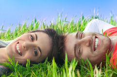 Happy couple lying in the grass Stock Photography