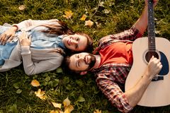 Happy couple lying on grass in autumn park while boyfriend. Is playing the guitar royalty free stock photo
