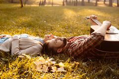Happy couple lying on grass in autumn park while boyfriend. Is playing the guitar stock image