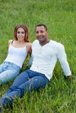 Happy couple lying on the grass in the field Stock Image