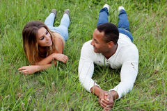 Happy couple lying on the grass in the field Royalty Free Stock Photos