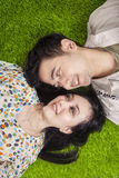 Happy couple lying on grass in the park Royalty Free Stock Photos