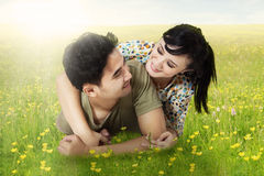 Happy couple lying on the grass in springtime Royalty Free Stock Image