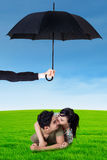 Happy couple lying on grass under umbrella. Photo of two young couple lying on the meadow under umbrella. Life and family insurance concept Stock Images