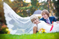 Happy couple are lying on the green grass Royalty Free Stock Photography