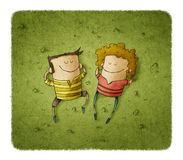 Happy couple lying on green grass with smiles Royalty Free Stock Photo