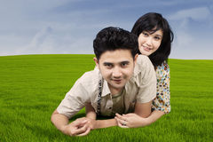 Happy couple lying on green grass Royalty Free Stock Image