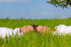 Happy couple lying on a meadow stock image