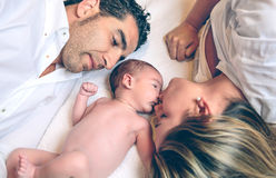 Happy couple lying over bed with their newborn Stock Image