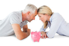 Happy couple lying with piggy bank Stock Photos